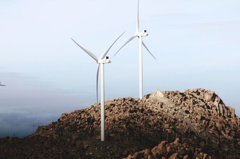 Low angle view of windmills on mountain against sky