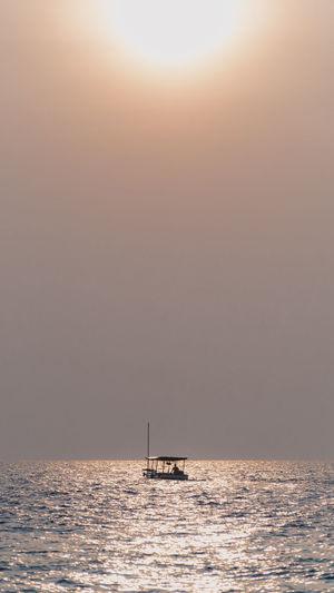 Silhouette boat sailing in sea against sky during sunrise in pari island, indonesia