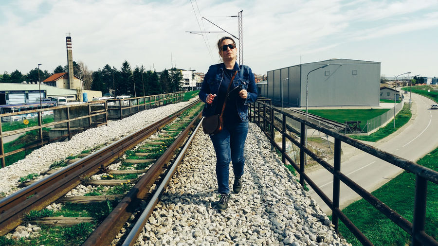 Full length of woman walking by railroad track