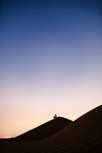 Silhouette person against clear sky at night