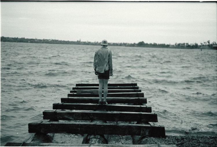 Rear View Of A Man Standing On Jetty Overlooking Lake