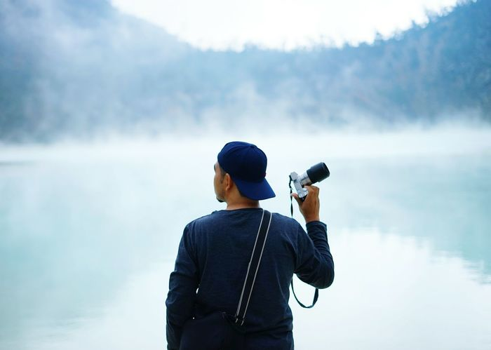 EyeEm Selects One Man Only Only Men Adult Adults Only One Person Lake Water Rear View People Men Fog Standing Outdoors Holding Mature Adult Exploration Day Nature Discovery Photographing