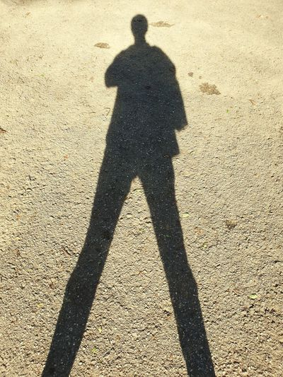 Shadow of man standing on road
