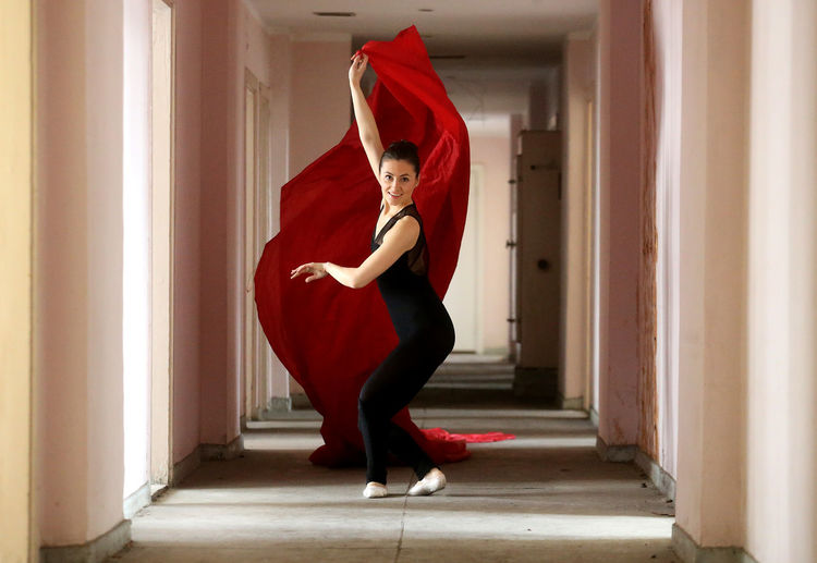 Full length portrait of young woman doing ballet dance with red fabric in corridor