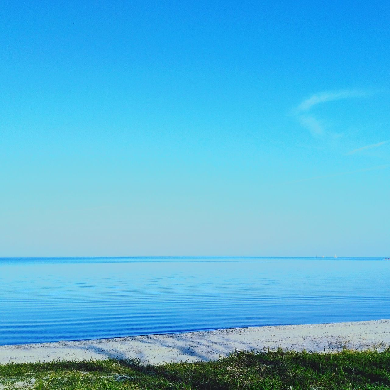 sea, blue, water, scenics, nature, tranquil scene, horizon over water, tranquility, beauty in nature, outdoors, day, clear sky, grass, no people, beach, sky, vacations