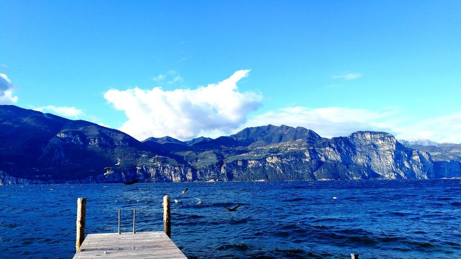 Scenic view of lake garda and mountains against blue sky