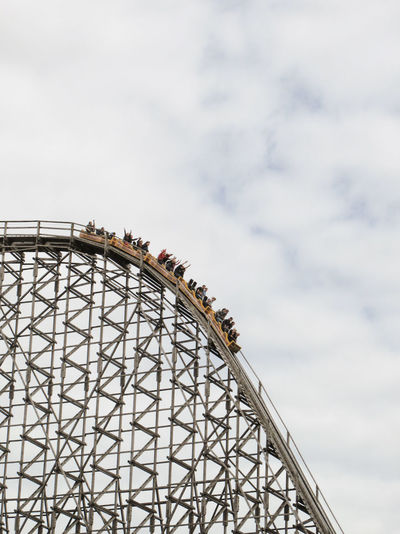 Low angle view of people on rollercoaster against cloudy sky