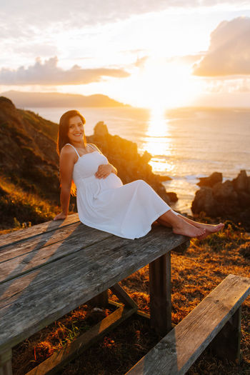 Woman sitting on wood by sea against sky during sunset