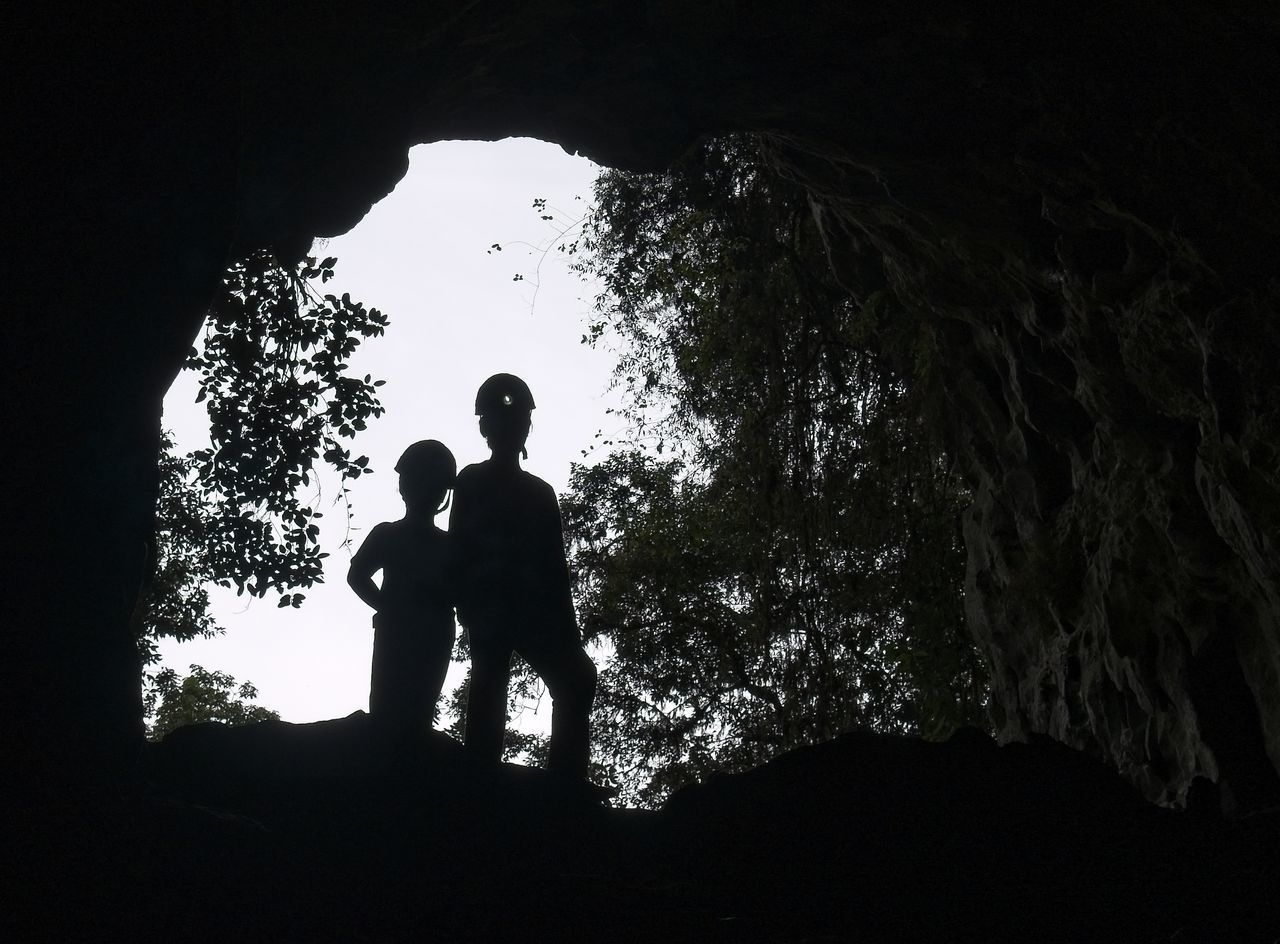 silhouette, tree, nature, real people, leisure activity, rock, plant, people, rock - object, lifestyles, standing, men, sky, solid, low angle view, day, outdoors, land, cave