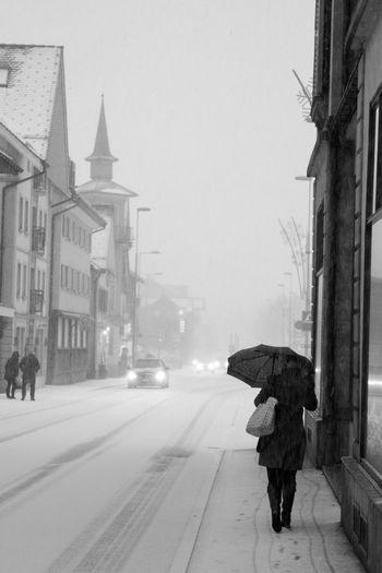 Swiss Town Walking Around City One Person Snow Snowing Street Streetphotography Switzerland Umbrella Walking Wintwer