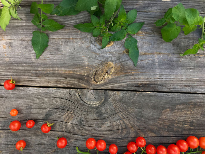 Directly above view of fresh cherry tomatoes and leaves on table