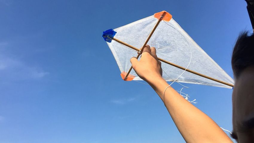Low Angle View Blue Holding One Person Day Real People Outdoors Sky Clear Sky Human Hand People