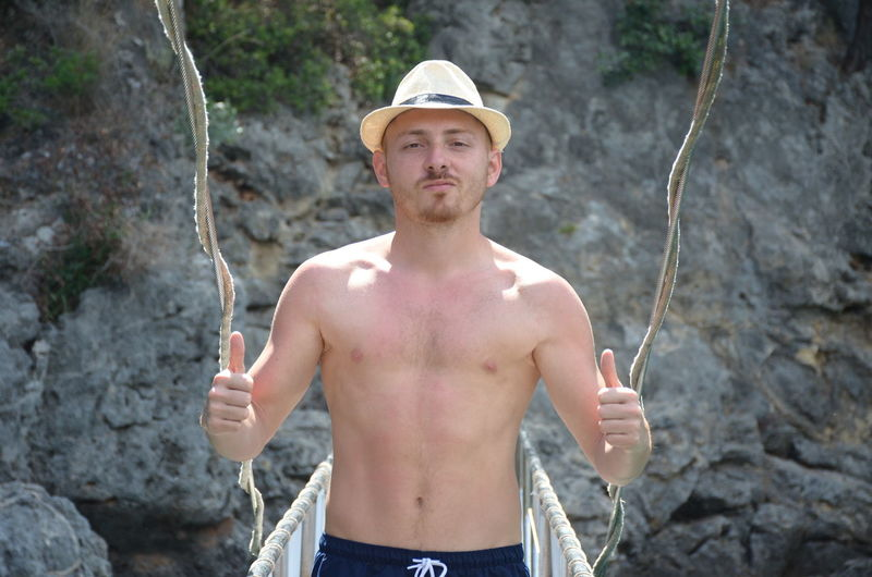 Portrait of shirtless man gesturing thumbs up on bridge against rock formation
