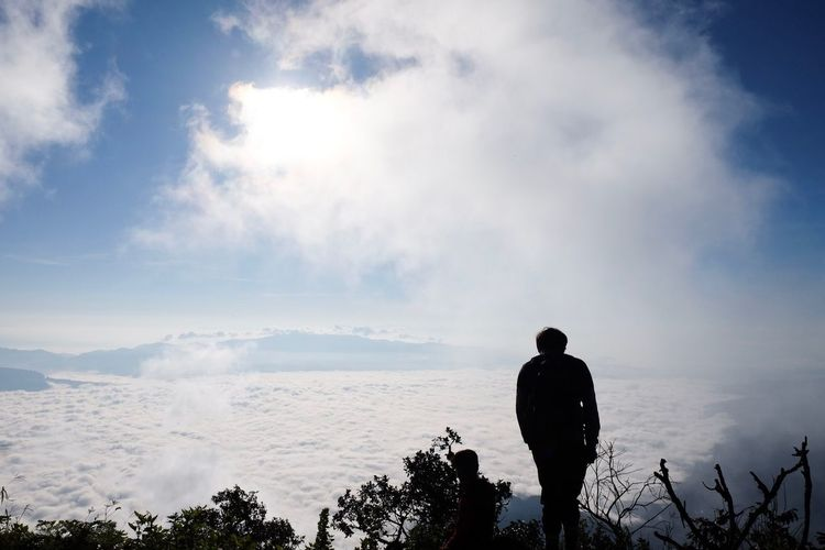 Silhouette man standing against sky during foggy weather