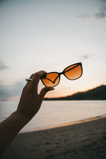 Woman holding sunglasses on beach against sky during sunset