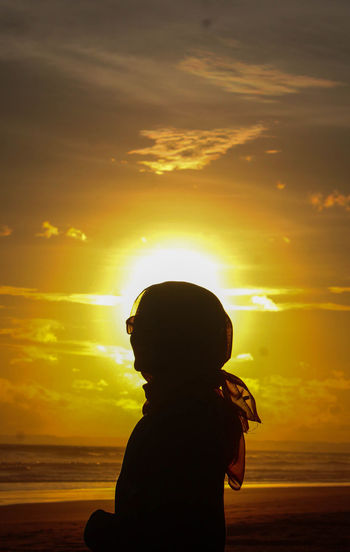 Silhouette woman on beach against sky during sunset