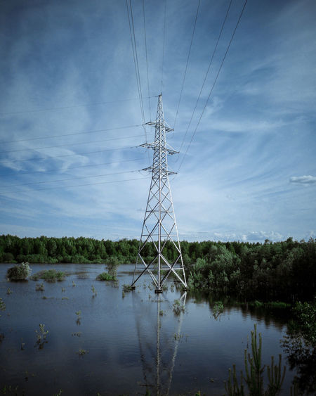 Electricity pylon by lake against sky