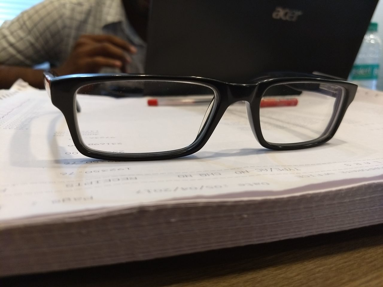 table, indoors, book, sunglasses, one person, eyeglasses, text, education, close-up, real people, day, human body part, human hand