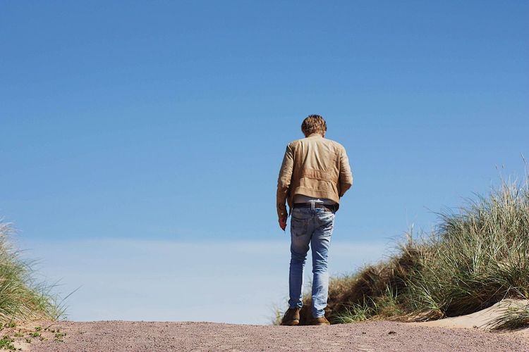 Rear view of man standing against clear sky