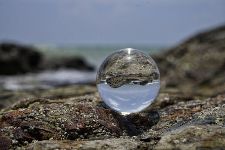 Solid Rock Rock - Object Sphere Nature Day No People Crystal Ball Close-up Sky Selective Focus Reflection Glass - Material Outdoors Focus On Foreground Ball Transparent Water Land Crystal