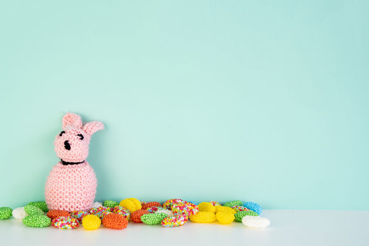 stuffed bunny toy with colored candy in front of an colored background, with space next to it Studio Shot Colored Background Animal Representation Indoors  Copy Space Toy Stuffed Toy Animal No People Food And Drink Still Life Food Representation Animal Themes Celebration Sweet Easter Sweet Food Bunny  Candy Colored Carp Pink Color Creativity Delicious