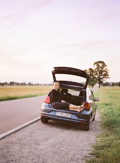 A woman sitting in the trunk of a German car on the side of the road. Camping Film Travel Adventure Adventure Time Car Environment Land Vehicle Landscape Mode Of Transportation Motor Vehicle Nature Outdoors Real People Relax Road Sitting Transportation Travel Women
