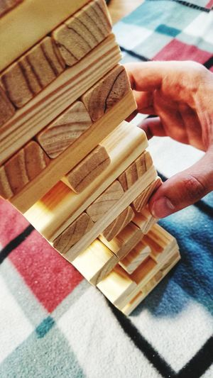Cropped hand of person playing with toy blocks on table