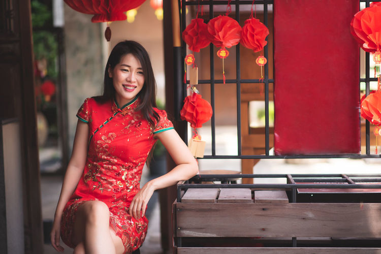 Smiling woman wearing red dress sitting outdoors