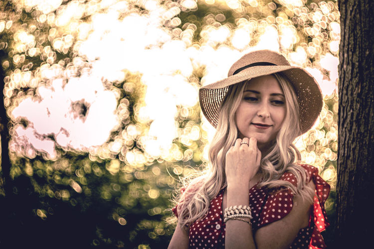 Smiling woman wearing hat standing by tree trunk