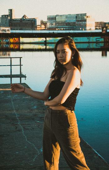 Portrait of teenage girl standing against water