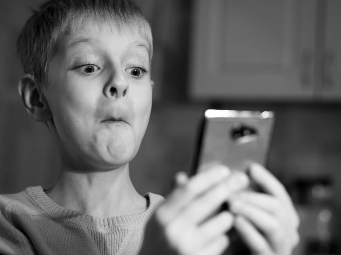 Close-up of shocked boy using phone at home