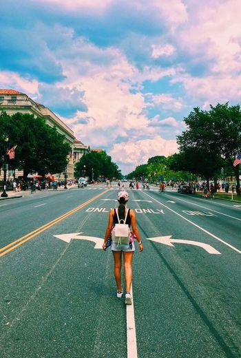 Rear view of girl walking on road against sky