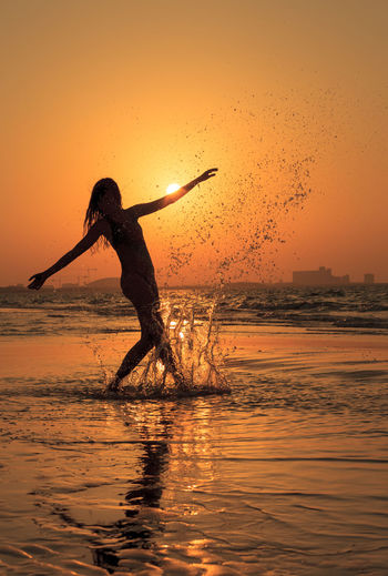 Silhouette Of Woman Dancing In Water At Sunset