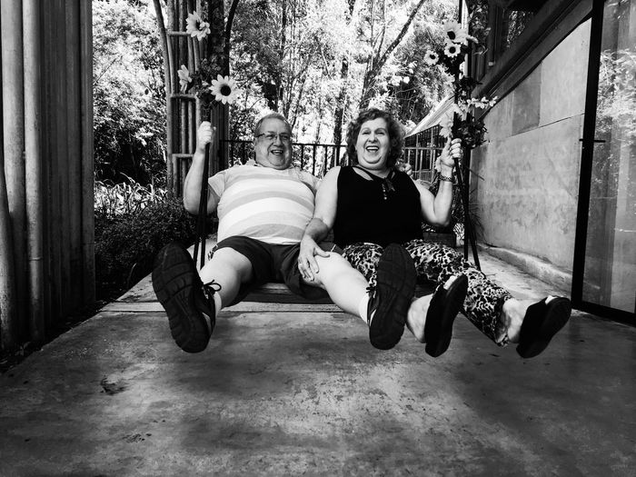 Portrait Of Happy Friends Swinging In Porch