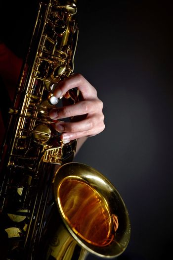 Close-Up Of Hand Holding Saxophone Against Black Background