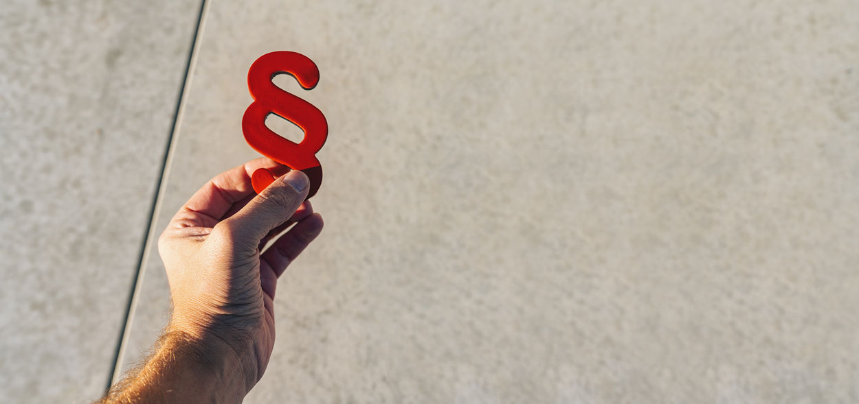Hand holds red paragraphs as a sign of justice and Iustitia / Justitia the Roman goddess of Justice, banner size, copyspace for your individual text. Wall - Building Feature Verdict Unrecognizable Person Text Symbol Structure Street Sign Shadow Rule Of Law Regulation Red Real People Prosecutor Process Personal Perspective Paragraph Symbol Paragraph Outdoors Order One Person Notary Method Message Men Listing Light Lifestyles Lawyer Law Justitia Justice Jury Jurisdiction Judicial Judgment Judge Imprint Idea Human Hand Human Body Part Hope Holding Hold Header Hand Glowing Gavel Focus On Foreground Finger Dsgvo Decision Day Criminal Court Copy Space Concrete Concept Communication Code Of Law Close-up Civil Right Business Body Part Banner Advocate