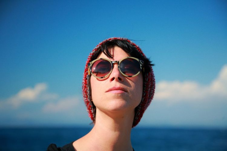 Portrait of woman wearing sunglasses against sky