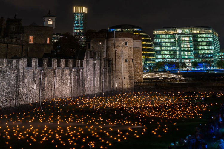 LONDON, UK - NOVEMBER 06, 2018: The Tower of London's moat has been filled with around 10,000 lit torches to mark the centenary of the end of the First World War. Architecture Built Structure Illuminated Night Building Exterior City Building No People Outdoors Reflection Glowing Travel Destinations Sky Motion Lighting Equipment City Life Office Building Exterior Skyscraper London Tower Of London Moat Armistice First World War Remembrance Day Torches