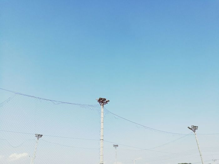 Low angle view of floodlights and netting against blue sky