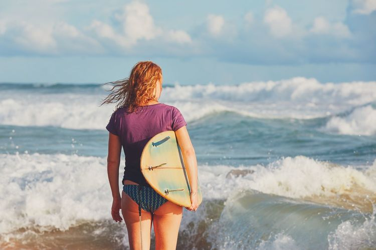 Surfer girl enjoying vacations on the tropical beach. Young woman with surfboard in Sri Lanka. Freedom Rear View Sri Lanka Surf Vacations Wave Woman Adventure Beach Coat Enjoying Life Enjoyment Girl Leisure Activity Lifestyles Nature Real People Recreational Pursuit Sea Sufer Surfboard Surfing Travel Destinations Water Young Adult