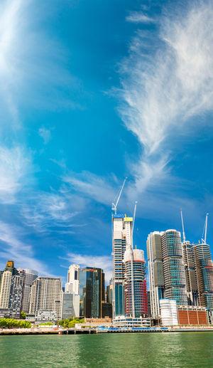 Modern buildings by sea against sky in city