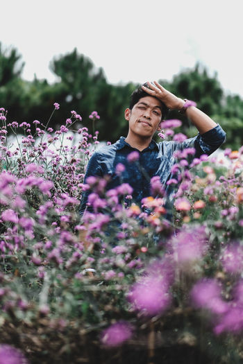 Midsection of person on purple flowering plants