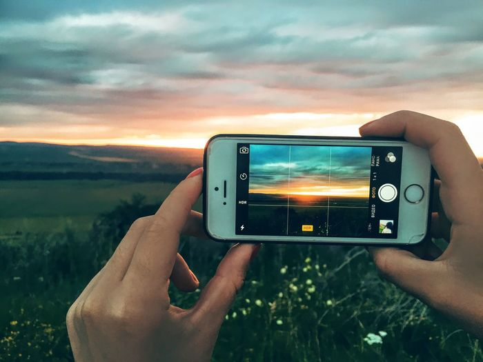 Midsection of person photographing camera on mobile phone against sky