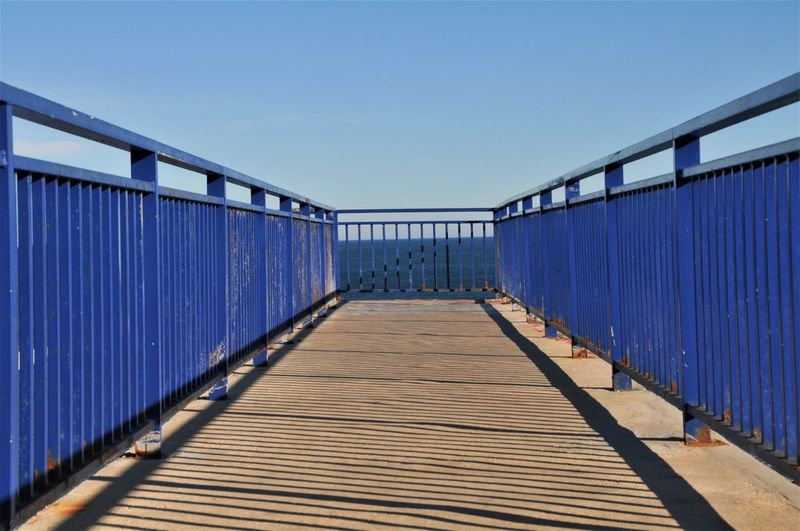 Footbridge against clear blue sky