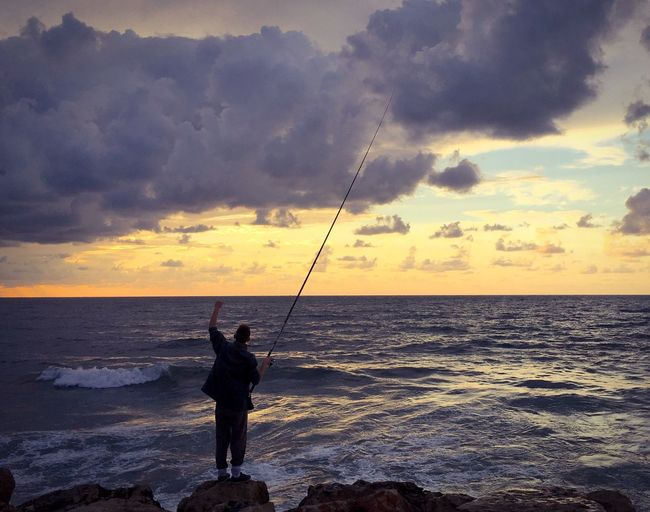 Man fishing in sea against sunset sky