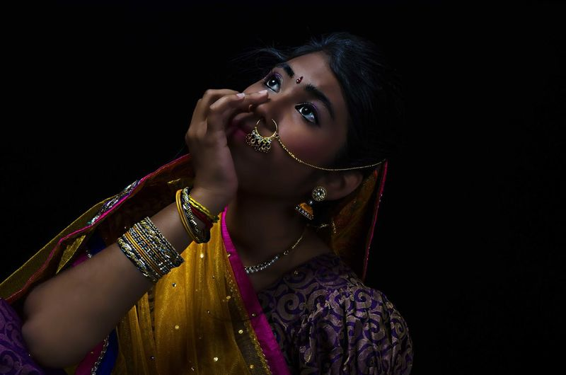 Thoughtful young woman wearing sari against black background