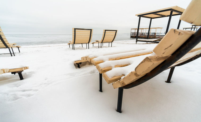 Empty chairs on snow covered land by sea against sky