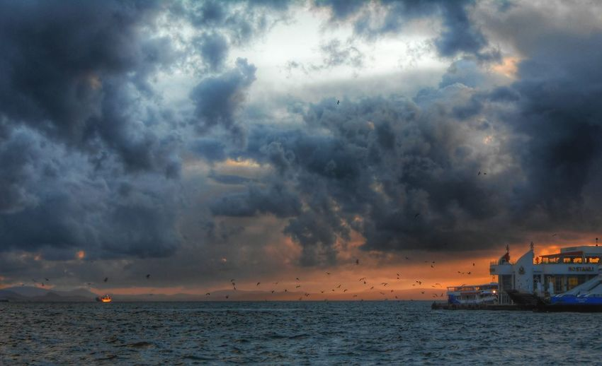 Ship sailing in sea against cloudy sky at dusk