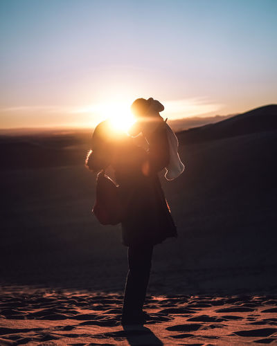 Full length side view of silhouette woman carrying son on sand dune during sunset