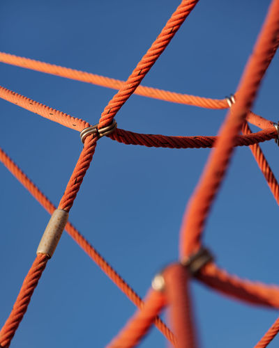 Low angle view of rope tied against sky